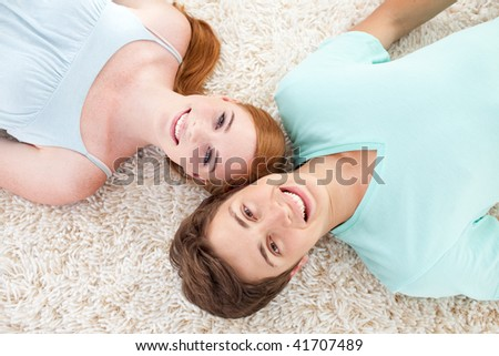 A couple of teenagers lying on floor talking and relaxing - stock photo