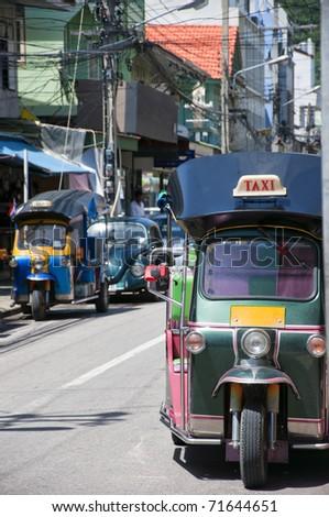 A couple of Thai tuk tuks sit parked awaiting tourists. - stock photo