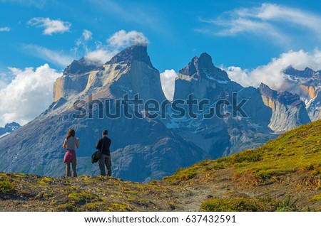 A couple of tourists / backpackers enjoying the view of the granite peaks in the Torres del Paine national park at sunset near Puerto Natales in Patagonia, Chile.