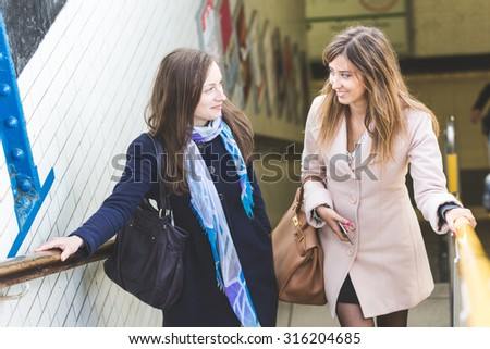A couple of women are talking while they are coming out from the train station. They are happy, smiling and are going to have a walk together in the city. It's winter and both are wearing a coat. - stock photo