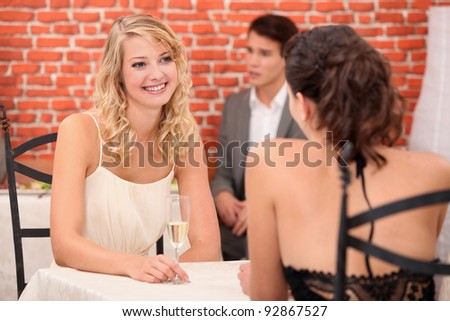 A couple of women drinking champagne in a restaurant. - stock photo