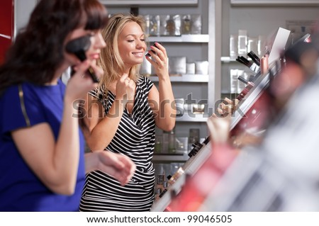 A couple of women enjoy themselves in a beauty store - stock photo