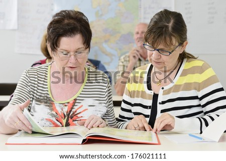 A couple of women in a classroom looking through an orange book.