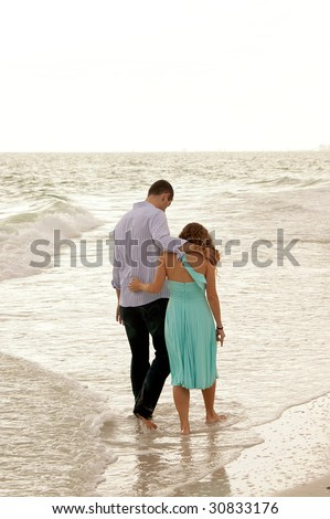 A couple of young adults walk through the water at the coastline of the gulf of mexico  in florida with their arms around each other, shot from behind. Copy space along the top - stock photo