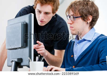 a couple of young employees in an office working together to achieve common goals - stock photo