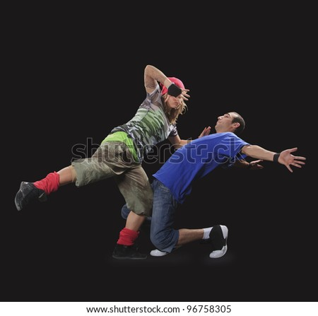 A couple of young man and woman dancing breakdance in the dark. - stock photo