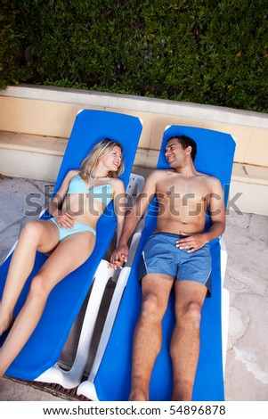 A couple on a holiday sitting by a pool - stock photo