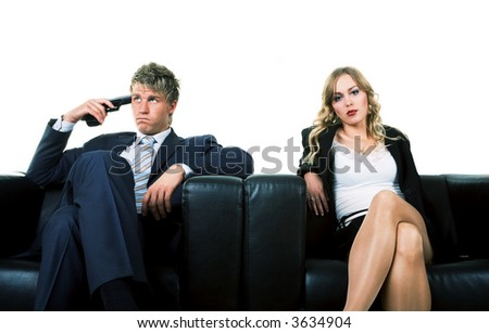 A couple on a sofa. He threatens to kill himself, she ignores him. A metaphor for divorce or lovesickness