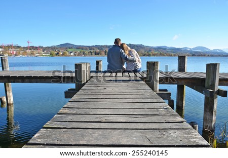 A couple on the wooden jetty at a lake. Switzerland - stock photo