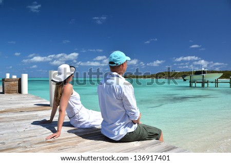 A couple on the wooden jetty. Exuma, Bahamas - stock photo