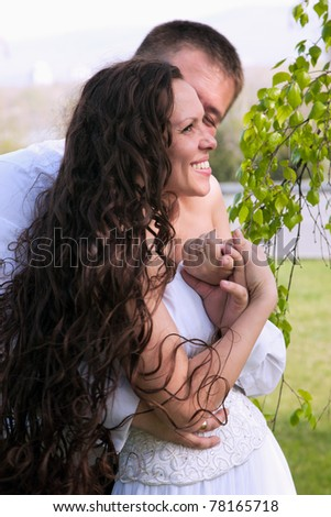 A couple on their wedding day kissing and laughing - stock photo