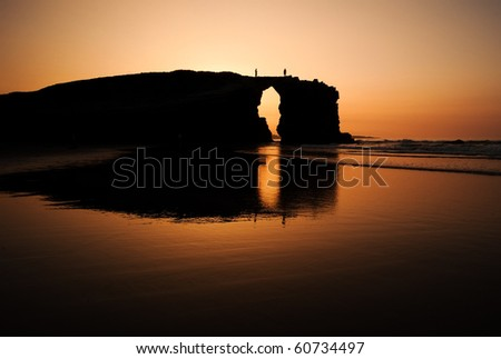 A couple over a big rock in a beach at sunset. Reflection of the rock is clearly visible. - stock photo