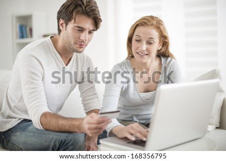 a couple paying with credit card on e-commerce - stock photo
