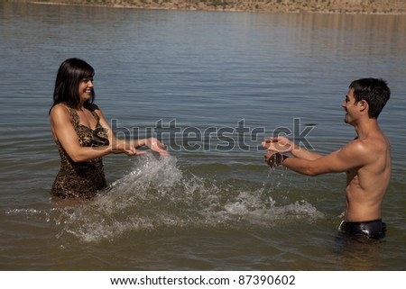 A couple playing in the water and splashing each other with smiles on their faces. - stock photo