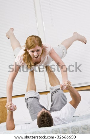 A couple playing on a bed.  The male is balancing the female in the air with his feet. She is laughing.  Vertically framed photo. - stock photo