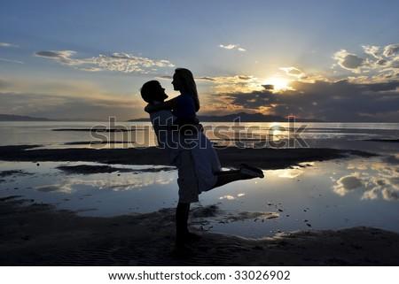A couple posing near a lake at sunset - stock photo