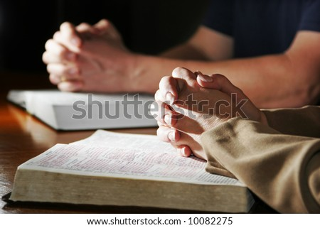 A couple prays together at a table as their hands rest upon their Holy Bibles (Shallow focus). - stock photo