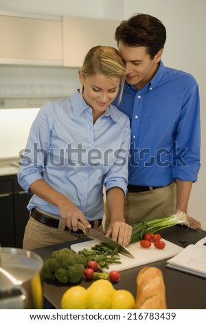 A couple preparing food in the kitchen.