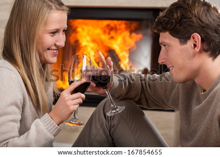 A couple proposing a tost by a fireplace with red wine - stock photo