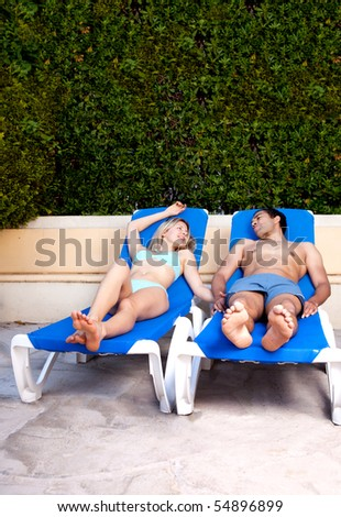 A couple relaxing at a hotel pool - stock photo