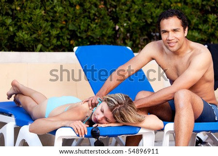 A couple relaxing by the pool, the man giving the woman a back massage - stock photo