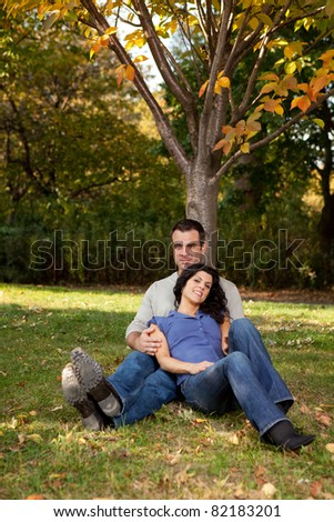 A couple relaxing in the park by a tree - stock photo