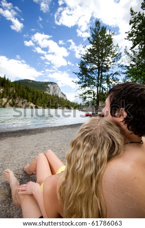A couple relaxing near a river in Banff, Canada - stock photo