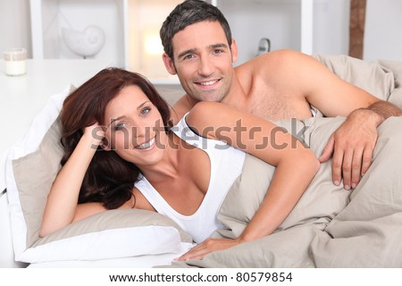 a couple reposing in bed in the morning - stock photo