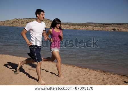 A couple running along the beach enjoying being out in the sun. - stock photo