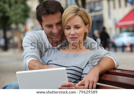 A couple seated on a bench and looking at something on a laptop.