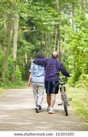 A couple senior asian talking while walking and exercising at a park - stock photo