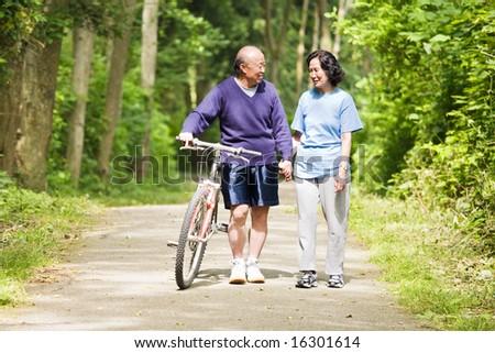 A couple senior asian talking while walking and exercising at a park - stock photo