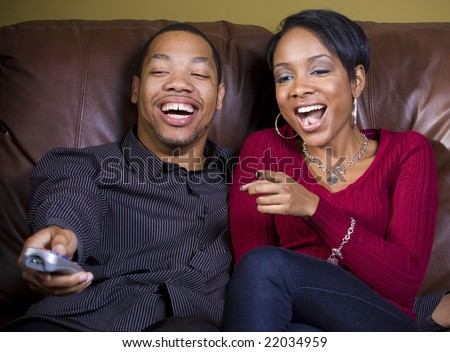 A couple shares a good laugh while watching something funny on TV