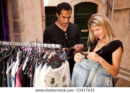 A couple shopping, looking at expensive clothes - shallow depth of field, focus on man - stock photo