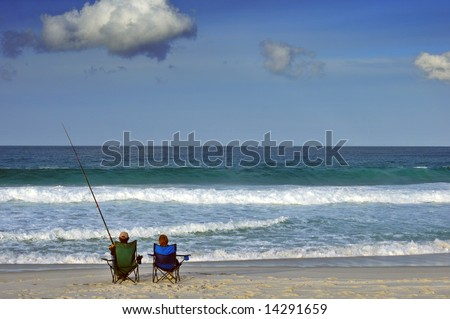 A couple sit on a beach the man fishing, the woman gazing out to sea..