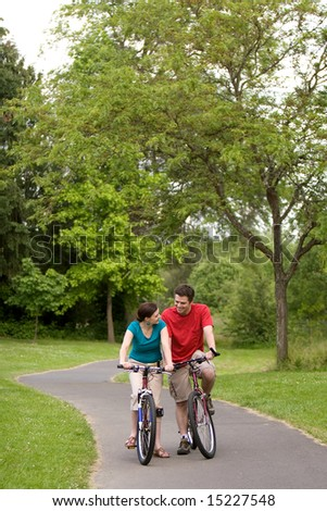 A couple, sit on bikes on a trail, staring at each other. vertically framed - stock photo