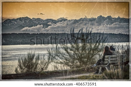 A Couple Sits on a Park Bench and Ponders Life while Looking out over the Puget Sound and Olympic Mountain Range with Vintage Edit, Scratches, and Dust - stock photo