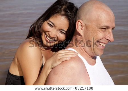 A couple sitting and touching with smiles on their faces.