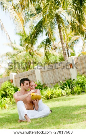 A couple sitting in the garden with a fresh young coconut drink