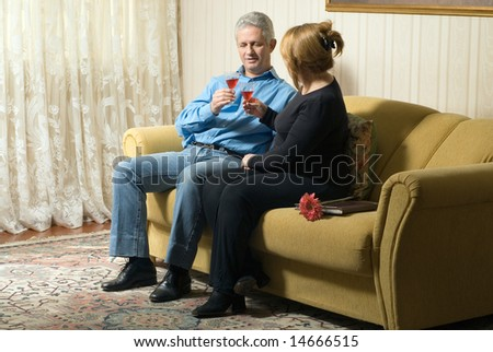 A couple, sitting next to each other on a couch, toast their drinks while a flower is near the woman. - horizontally framed