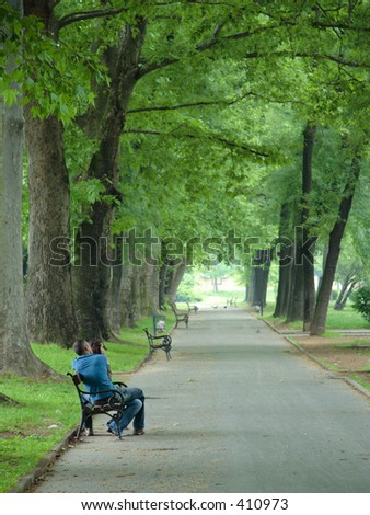 A couple sitting on a bench in the park - stock photo