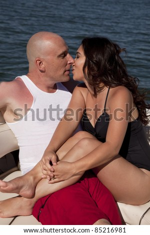 A couple sitting on a boat in the water cuddling and getting ready to kiss.