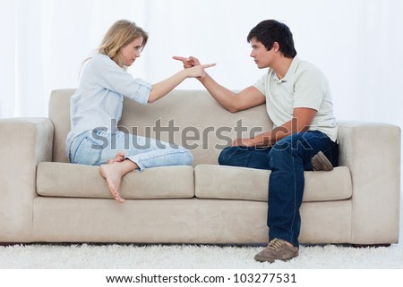 A couple sitting on a couch are looking at each other and pointing