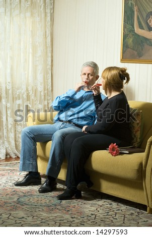 A couple sitting on a couch, drinking out of champagne glasses, staring at each other. - vertically framed - stock photo