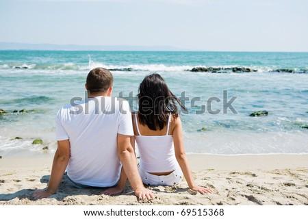 A couple sitting on beach - stock photo