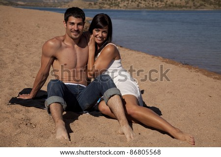 A couple sitting on the beach holding each other. - stock photo