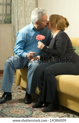 A couple sitting on the couch, holding a pink flower, kissing. - vertically framed - stock photo