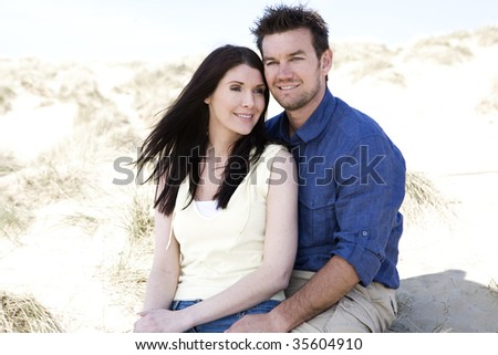 A couple sitting together on the beach, ""