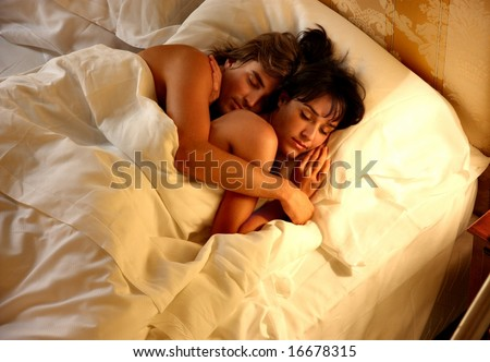 a couple sleep in a bed - stock photo