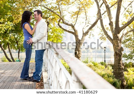 A couple smiling and looking at eachother in a park - stock photo